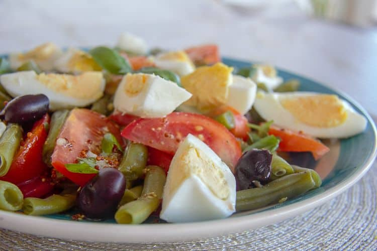 A salad made with green beans, eggs, tomatoes and olives.