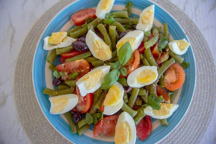 A main salad of green beans, tomatoes, olives and hard boiled eggs