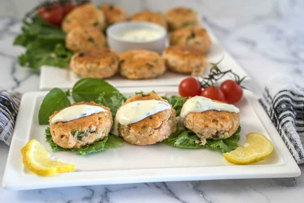 salmon patties with lemon slices and a sauce over them.