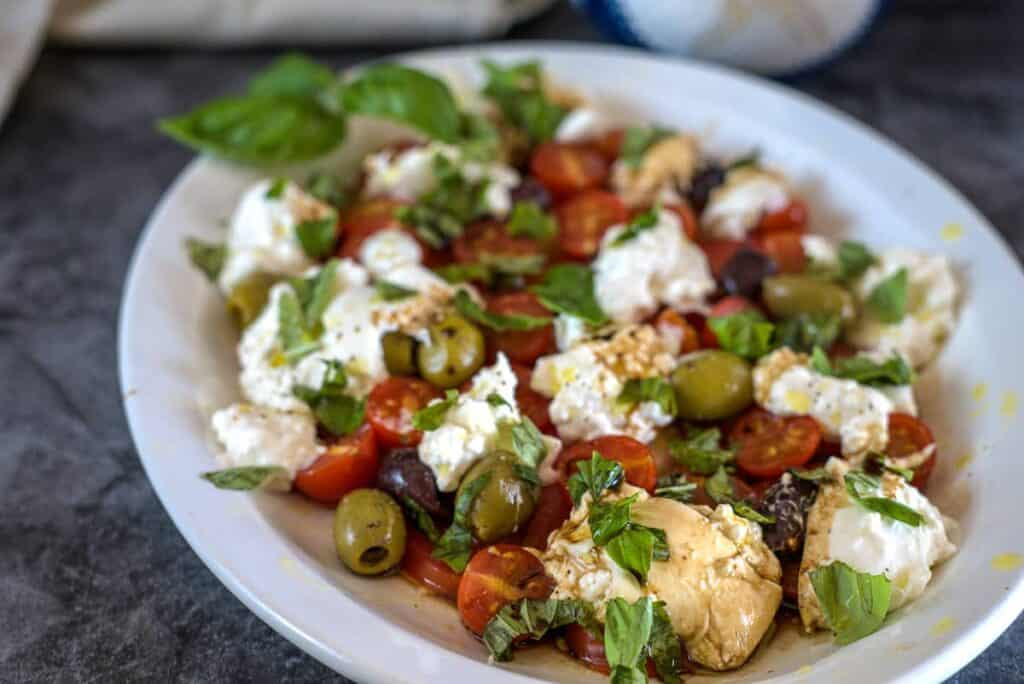 olives, tomatoes with burrata cheese and basil leaves