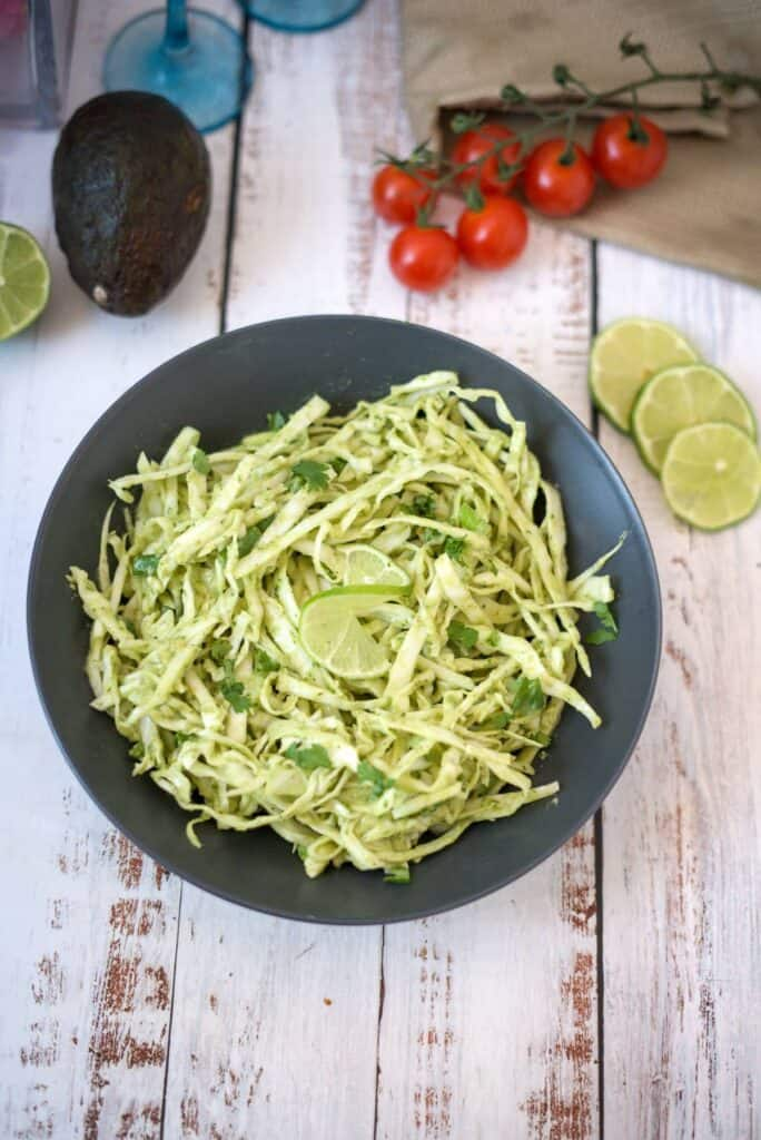 avocado coleslaw in a bowl with limes