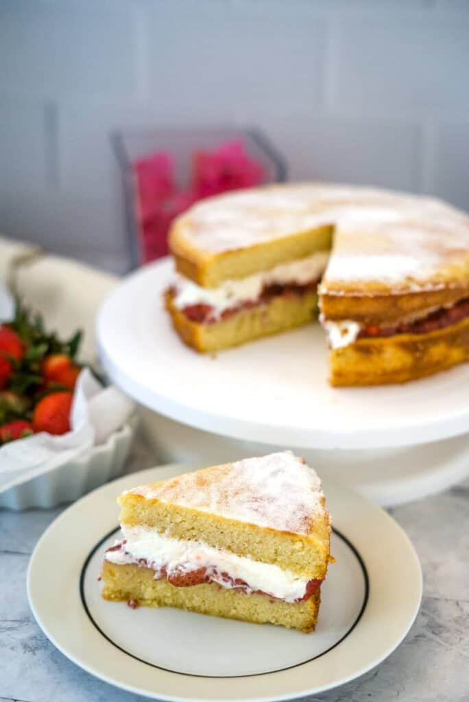 slice of victoria sponge cake with strawberries and cream